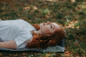 A red headed woman relaxing in the grass
